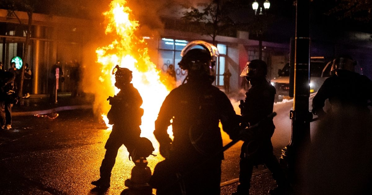 Portland police walk past a fire started by a Molotov cocktail on Sept. 23, 2020, in Portland, Oregon. Violent protests erupted across the nation following the results of a grand jury investigation into the police shooting death of Breonna Taylor.