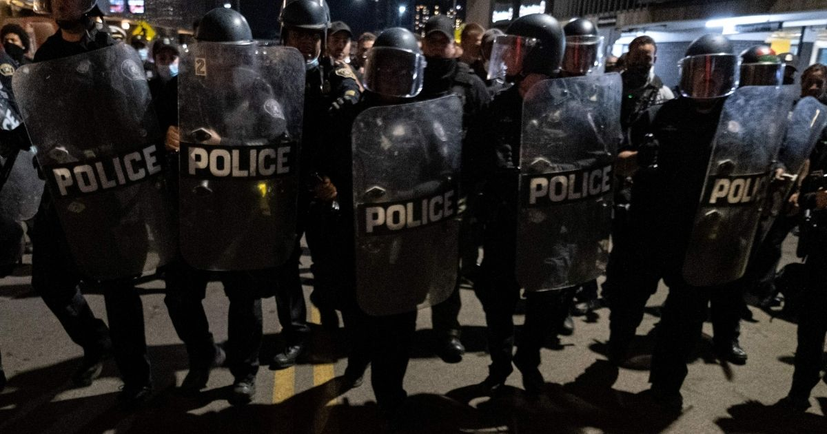 Riot police officers watch as people protest in the city of Detroit, Michigan, on May 29, 2020.