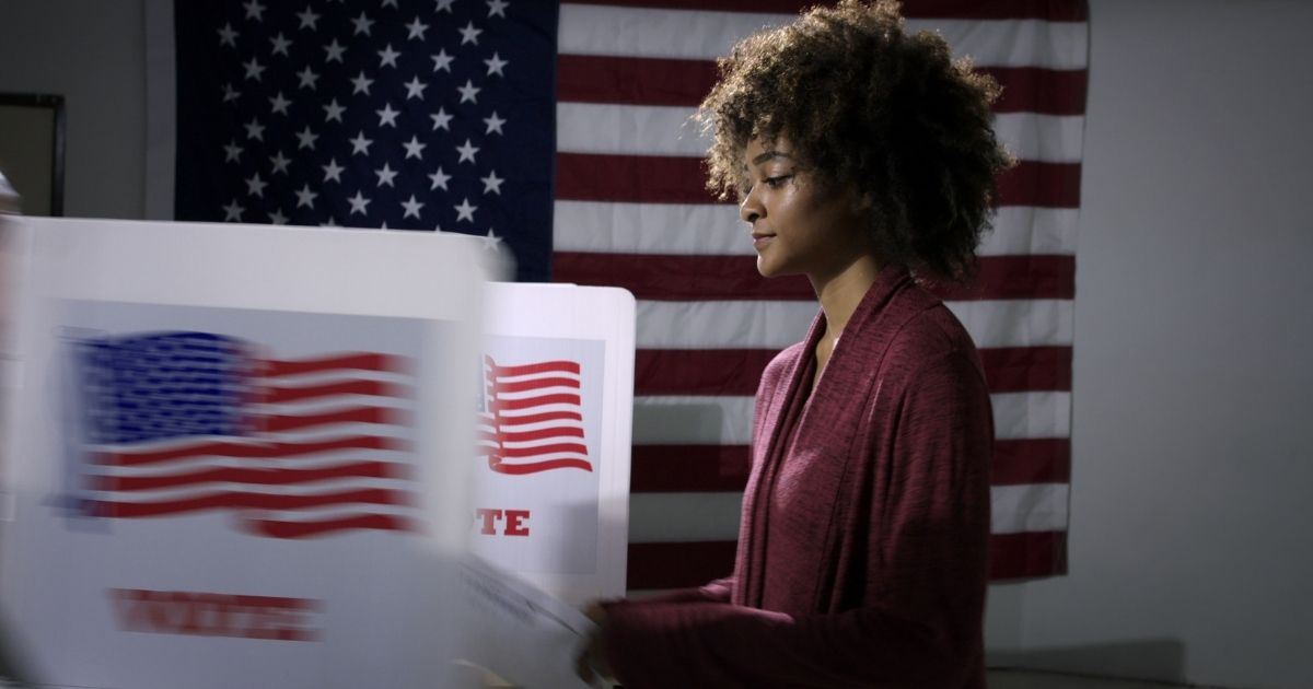 A young woman prepares to vote in the stock image above.