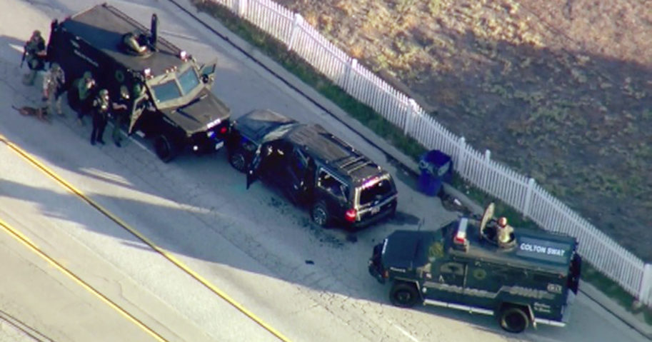 In this Dec. 2, 2015, file photo, armored vehicles surround an SUV following a shootout in San Bernardino, California.
