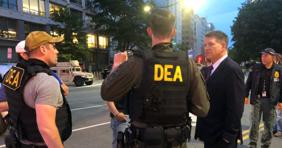 In this June 3, 2020, photo, acting head of the Drug Enforcement Administration Timothy Shea, right, visits with DEA agents at a checkpoint in Washington.