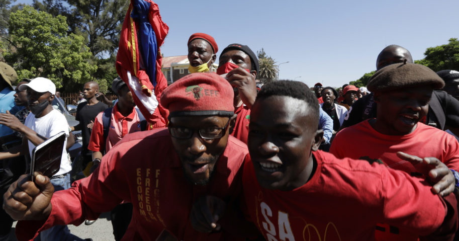 Members of the Economic Freedom Fighters protest Friday outside the magistrates court in Senekal, South Africa, where two suspects were to appear on charges of killing a white farmer.