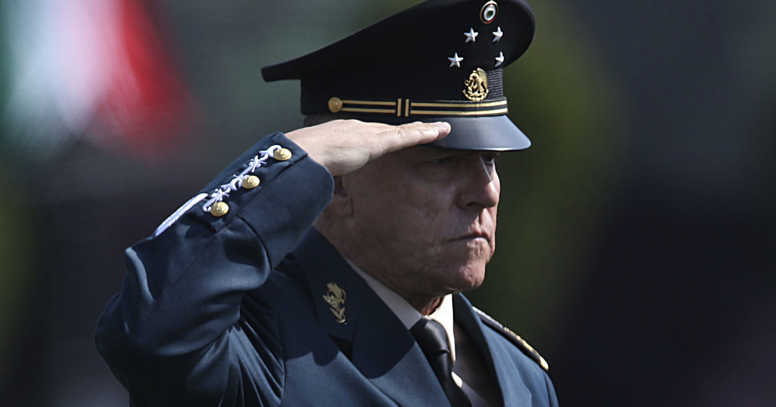 In this April 16, 2016, file photo, Mexico's Defense Secretary Gen. Salvador Cienfuegos Zepeda salutes soldiers at a military camp in Mexico City.