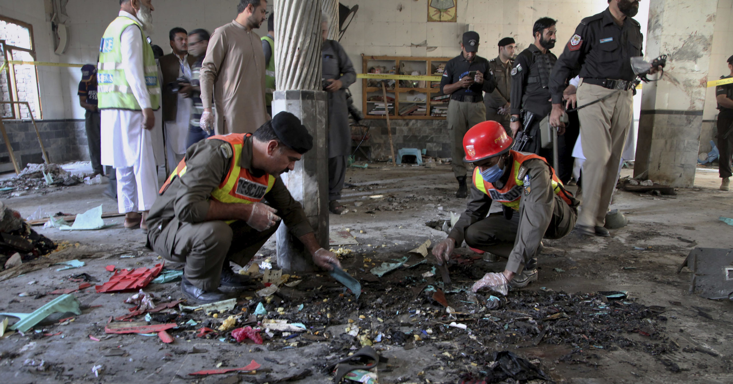 Rescue workers and police officers examine the site of a bomb explosion in an Islamic school in Peshawar, Pakistan, on Oct. 27, 2020.
