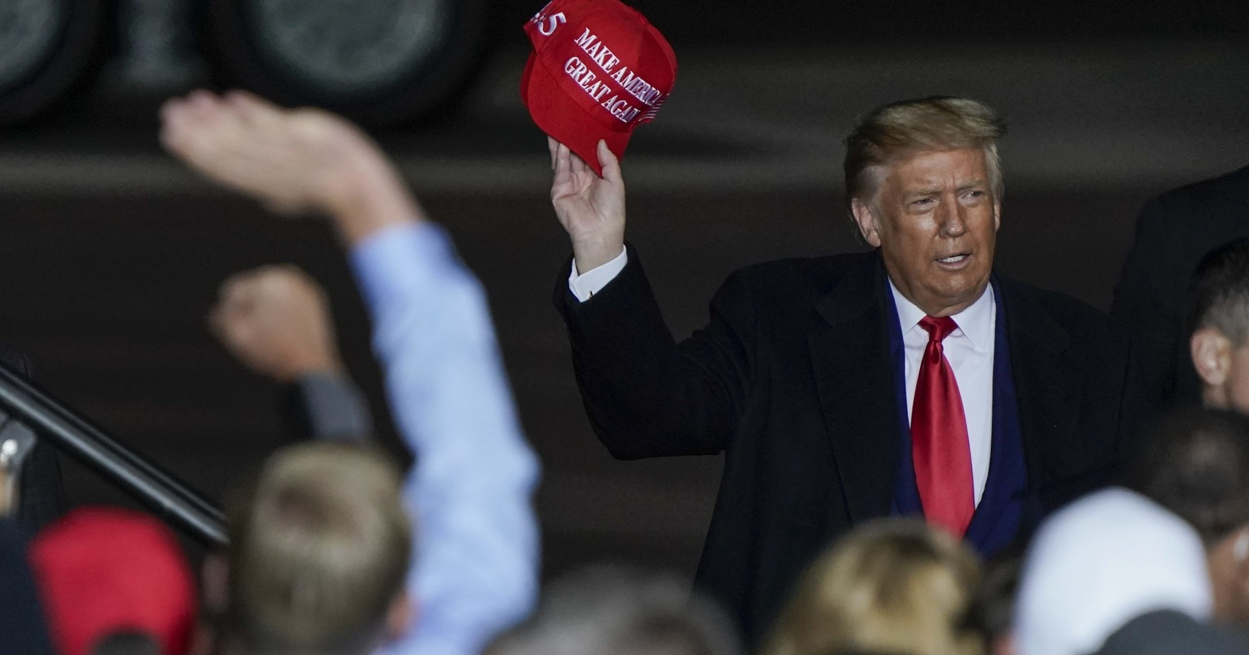 President Donald Trump throws a hat to the crowd after speaking at a campaign rally at the Central Wisconsin Airport in Mosinee, Wisconsin, on Sept. 17.