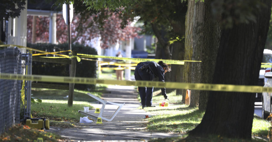 A Rochester police technician picks up items as evidence near the home where a fatal shooting took place on Sept. 19, 2020, in Rochester, New York.