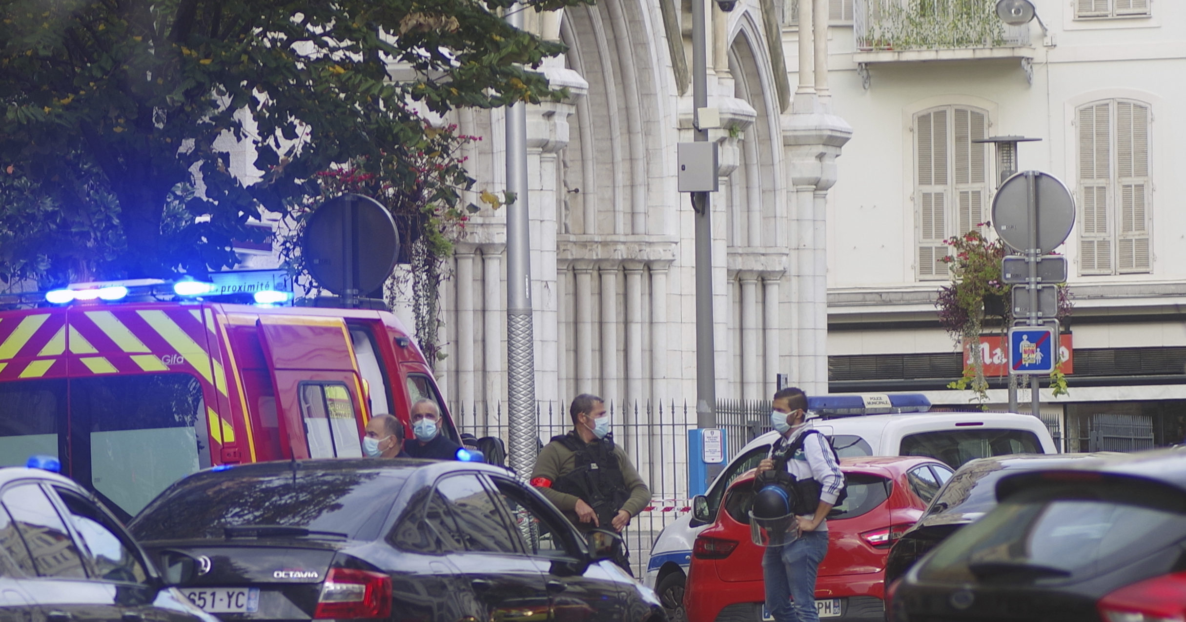 French police officers stand next to the Notre Dame Basilica after a deadly knife attack in Nice, France, on Thursday.