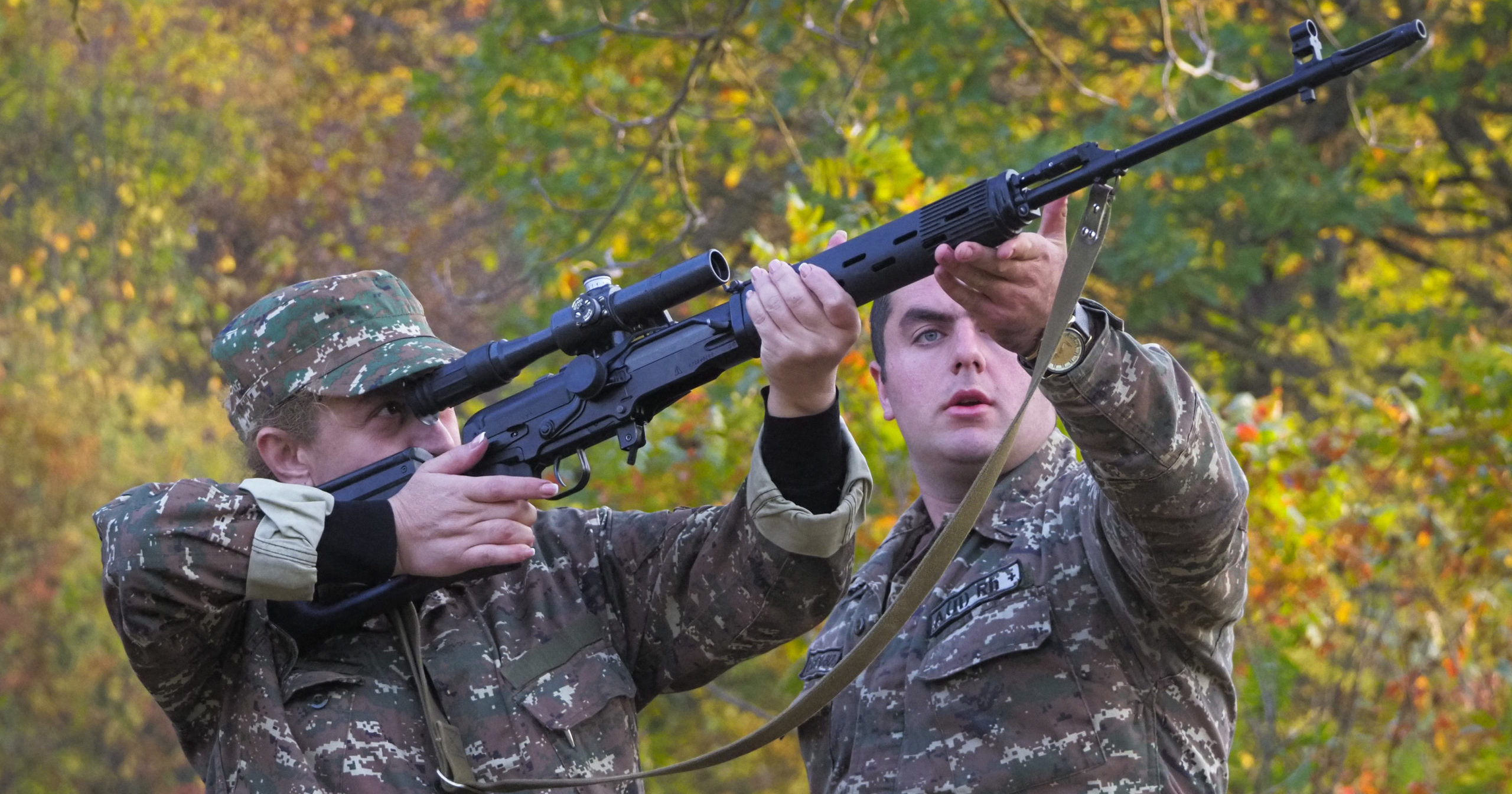 An instructor helps a volunteer soldier practice with a sniper rifle at a military base during a conflict in the separatist region of Nagorno-Karabakh on Oct. 27, 2020.
