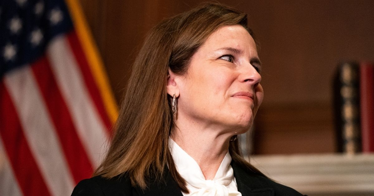 Judge Amy Coney Barrett, President Donald Trump's nominee for Supreme Court, poses for a photo before a meeting with Montana GOP Sen. Steve Daines at the United States Capitol Building on Oct. 1, 2020, in Washington, D.C.