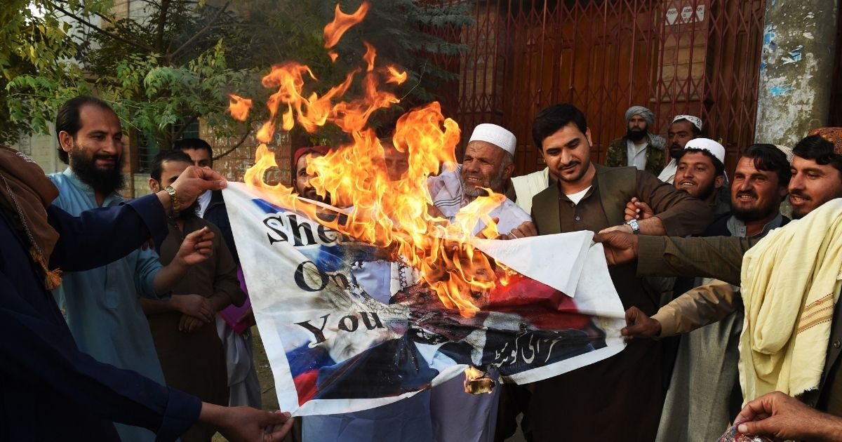 Demonstrators in Quetta, Pakistan, burn a poster featuring an image of French President Emmanuel Macron with a footprint over his face Monday.