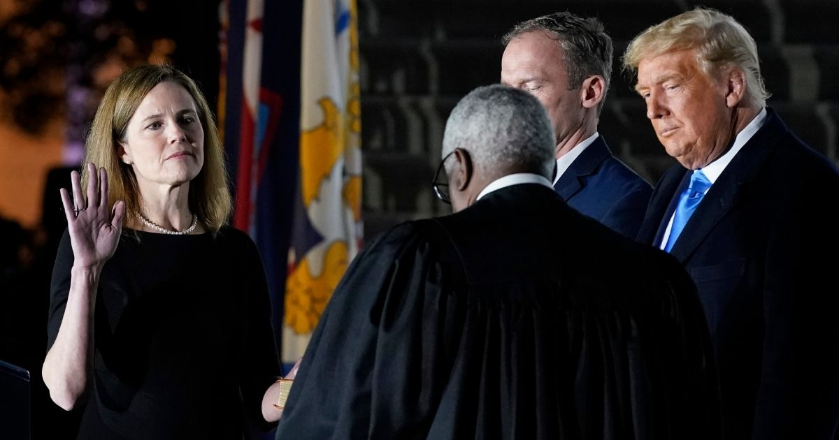 President Donald Trump watches as Supreme Court Justice Clarence Thomas administers the constitutional oath to new Justice Amy Coney Barrett on the South Lawn of the White House in Washington on Monday.