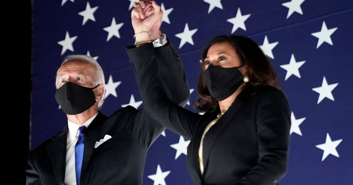 Democratic presidential candidate Joe Biden and his running mate, Sen. Kamala Harris of California, join hands during the Democratic National Convention at the Chase Center in Wilmington, Delaware, on Aug. 20.