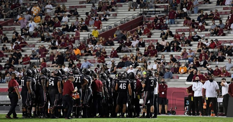 Socially distanced fans look on as the South Carolina Gamecocks huddle during a stoppage in play of their football game against the Tennessee Volunteers at Williams-Brice Stadium Columbia, South Carolina, on Saturday.