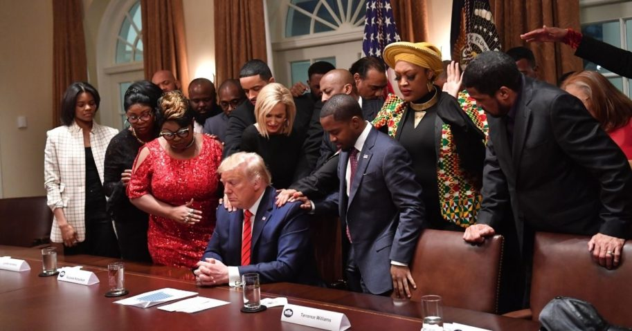 President Donald Trump, center, stands in a prayer circle with African-American leaders in the Cabinet Room of the White House in Washington, D.C., on Feb. 27, 2020.