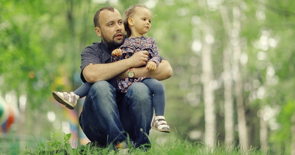 A father holds his daughter in the stock image above.