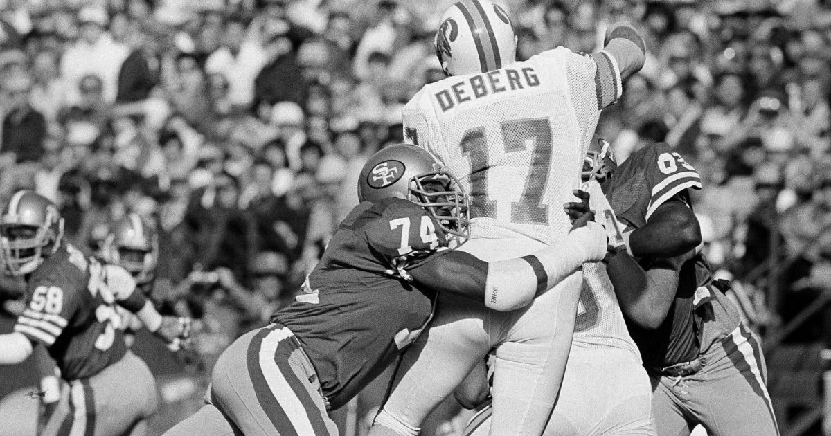 In this Nov. 18, 1984, file photo, San Francisco 49ers defensive end Fred Dean (74) brings down Tampa Bay Buccaneers quarterback Steve DeBerg (17) for a loss during the first half of their NFL game at Candlestick Park, in San Francisco. Dean, the fearsome pass rusher who was a key part of the launch of the San Francisco 49ers' dynasty, has died. He was 68.