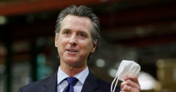 California Gov. Gavin Newsom holds a face mask as he urges people to wear them to fight the spread of the coronavirus during a news conference in Rancho Cordova, California, on June 26, 2020.