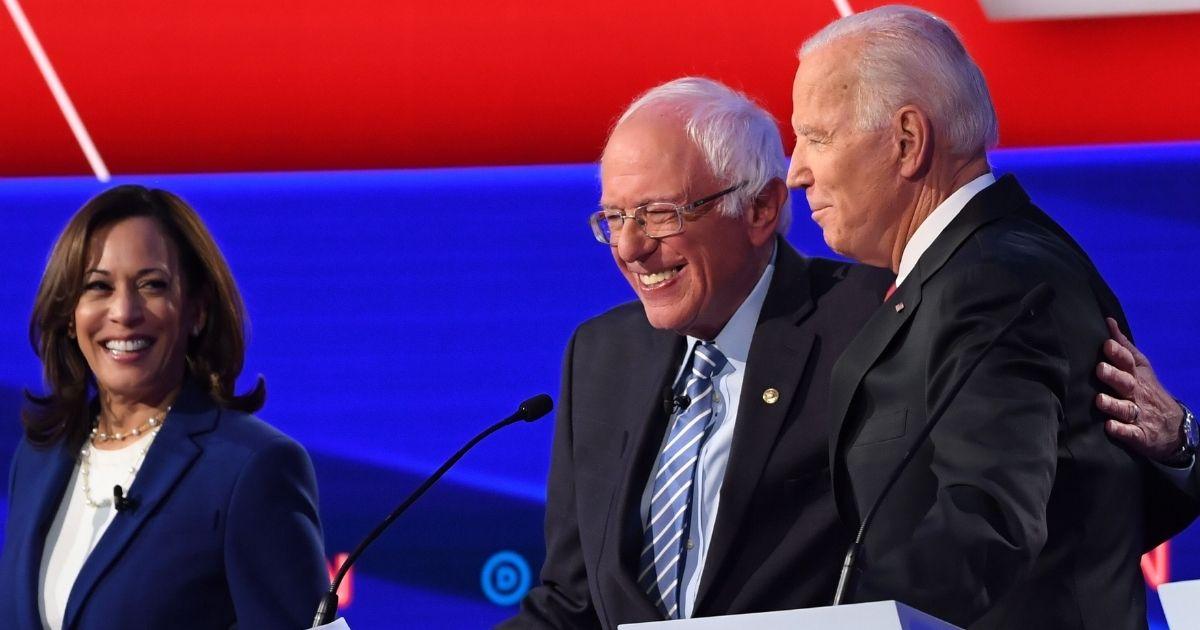 California Sen. Kamala Harris, Vermont Sen. Bernie Sanders and former Vice President Joe Biden smile during a Democratic primary debate at Otterbein University in Westerville, Ohio, on Oct. 15, 2019.