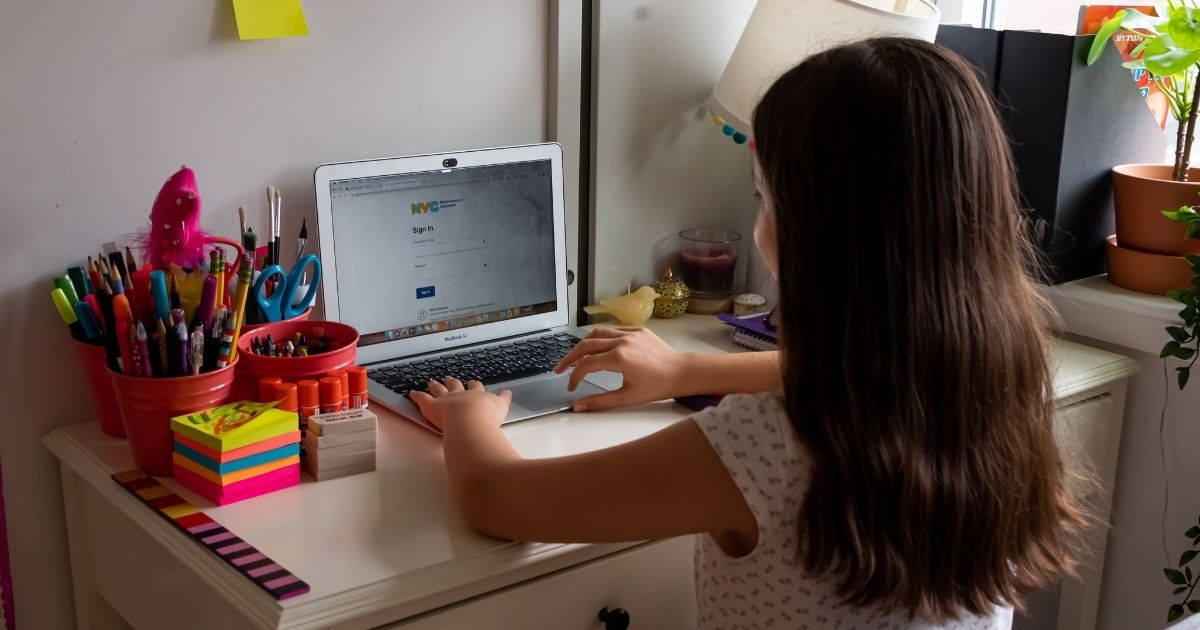 A kid sits in front of her computer as she does homeschooling at her house in the above stock photo.