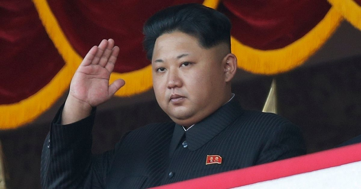 Kim Jong Un gestures as he watches a military parade