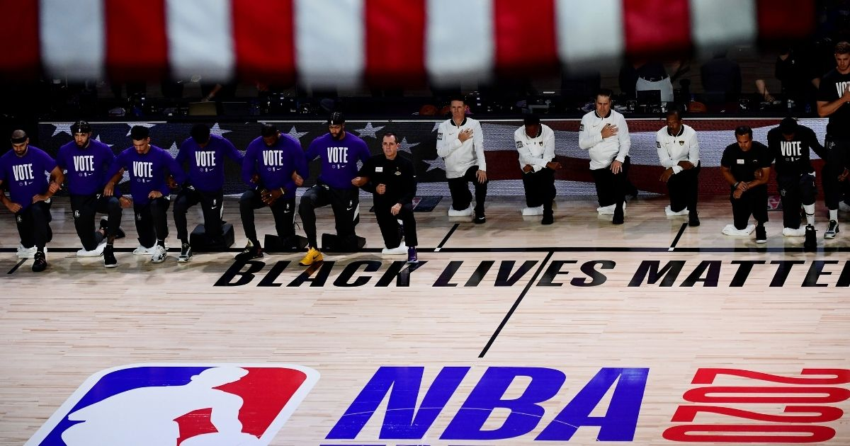 Members of the Los Angeles Lakers kneel during the national anthem before Game 2 of the 2020 NBA Finals against the Miami Heat at AdventHealth Arena in Lake Buena Vista, Florida, on Oct. 2, 2020.