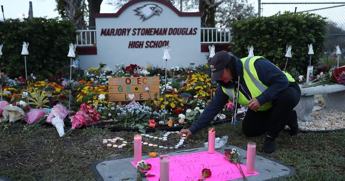 Wendy Behrend, a school crossing guard who was on duty when a shooter opened fire in Marjory Stoneman Douglas High School, pays her respects at a memorial for those killed one year after the shooting on Feb. 14, 2019, in Parkland, Florida.