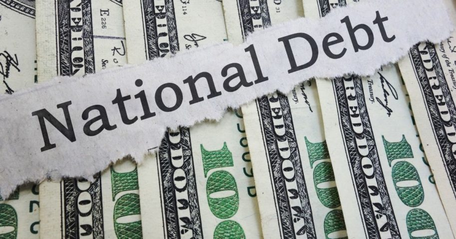 A photo of bills representing the national debt is pictured above.