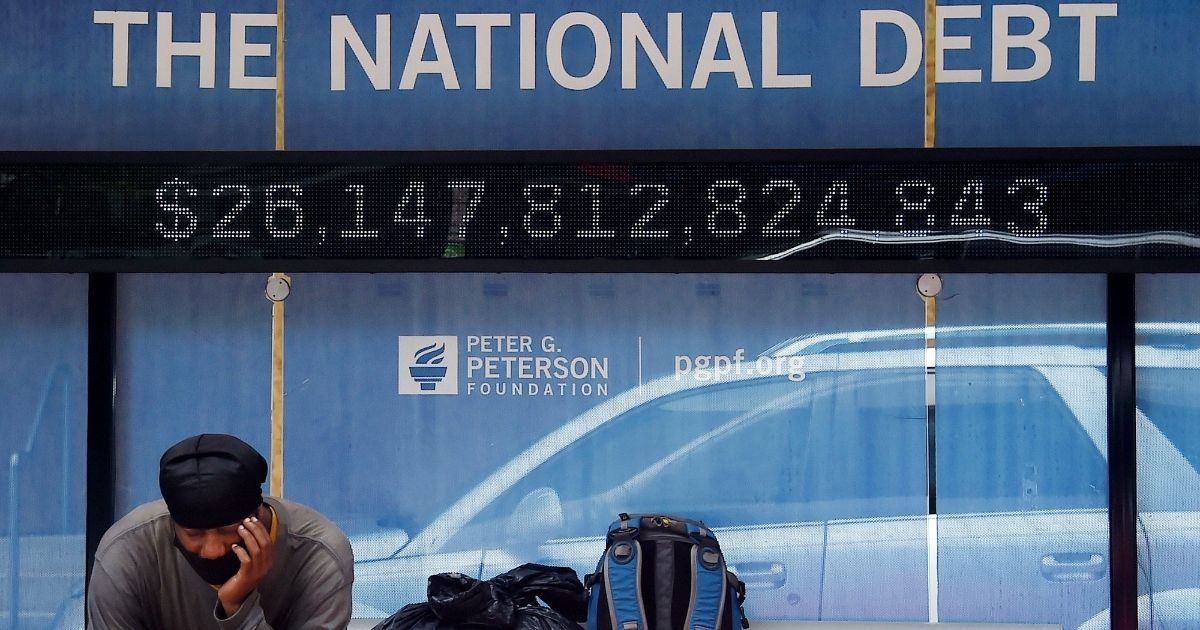 A man waits at a bus stop that displays the national debt of the United States on June 19, 2020, in Washington, D.C.