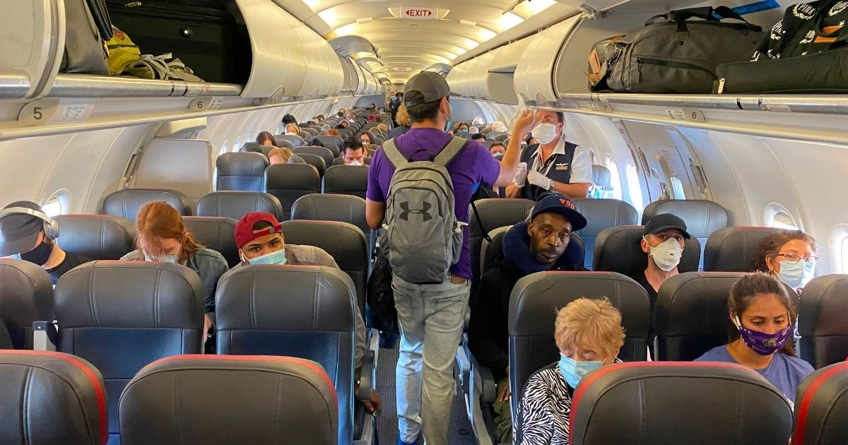 Passengers, most wearing facemasks, board an American Airlines flight from New York City to Charlotte, North Carolina, on May 3, 2020.