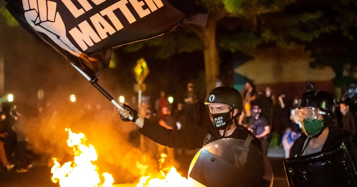 Protesters gather in front of a fire near the North police precinct during a protest on Sept. 6, 2020, in Portland, Oregon.