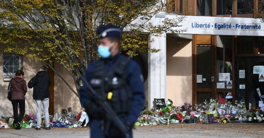 An officer stands guard Tuesday as people look at flowers placed outside the Bois d'Aulne secondary school in Conflans-Sainte-Honorine, France, in honor of slain history teacher Samuel Paty.