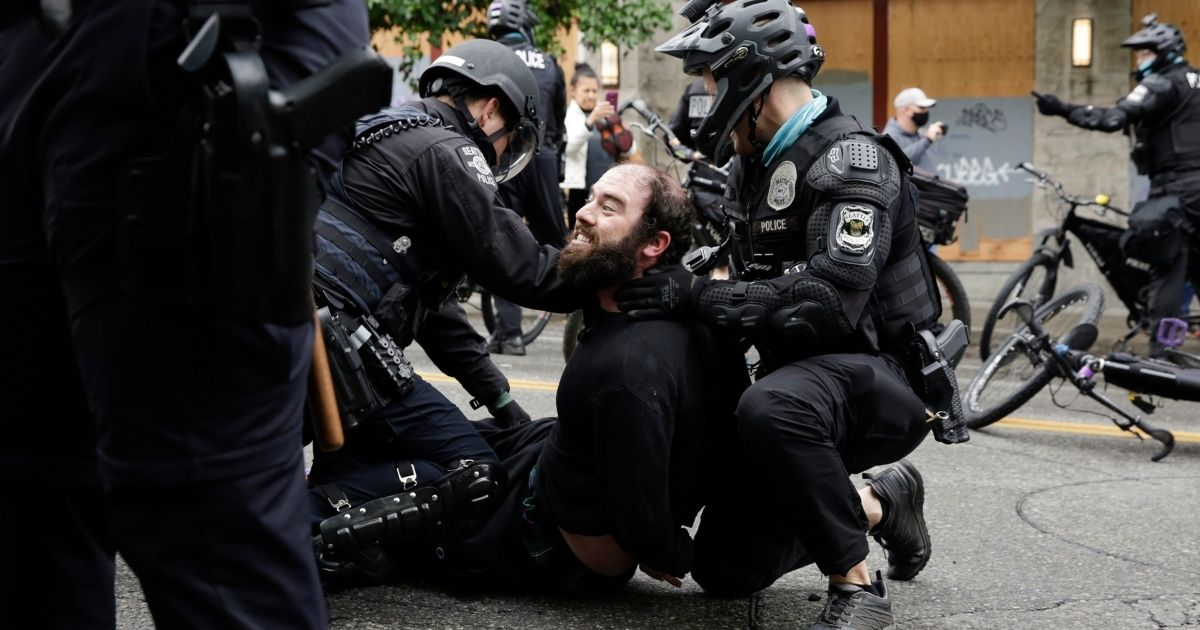 Seattle police arrest a demonstrator who was blocking the intersection of East Pine Street and 11th Avenue after officers cleared the Capitol Hill Occupied Protest zone and retook the department's East Precinct on July 1.