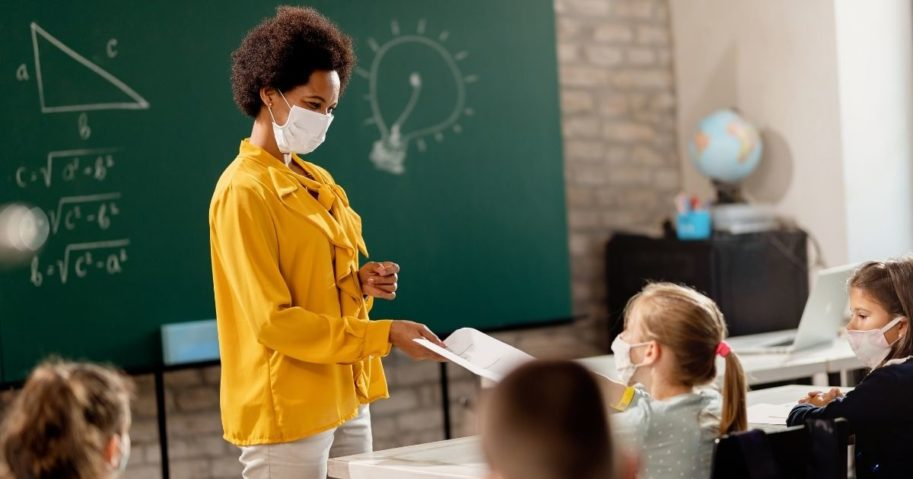 A teacher interacts with a student in the stock image above.