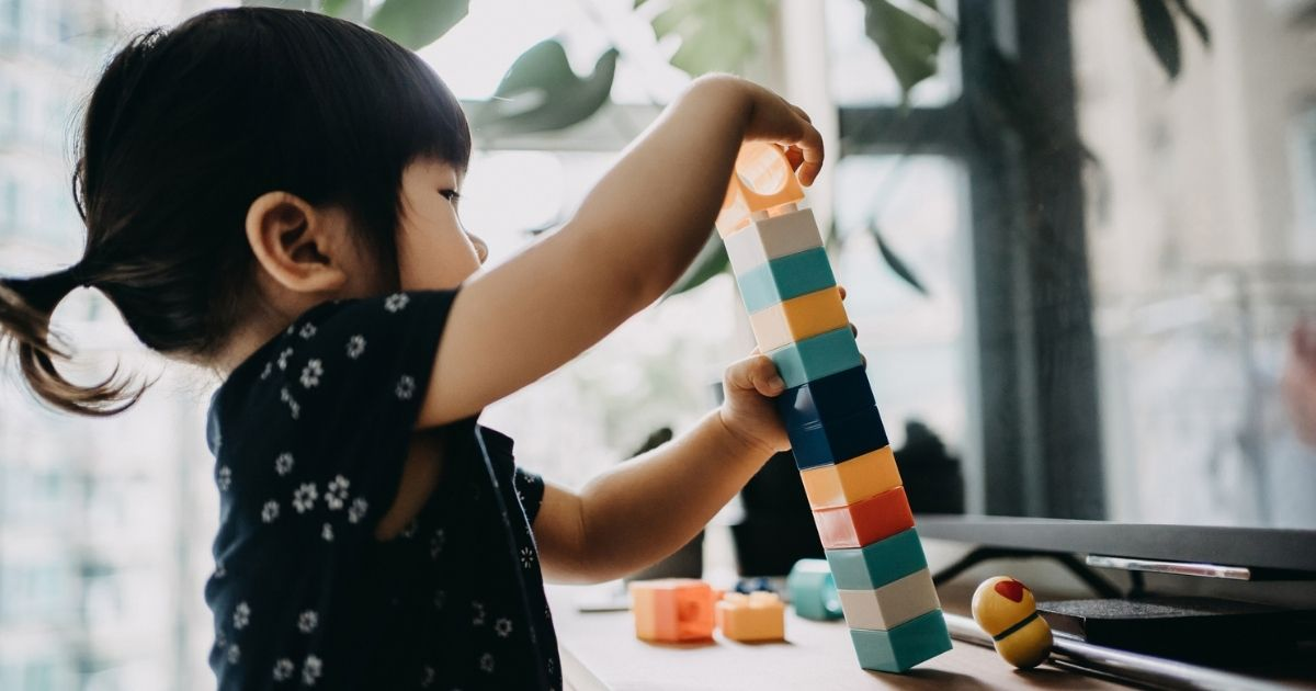 A toddler plays with toys in the above stock image.
