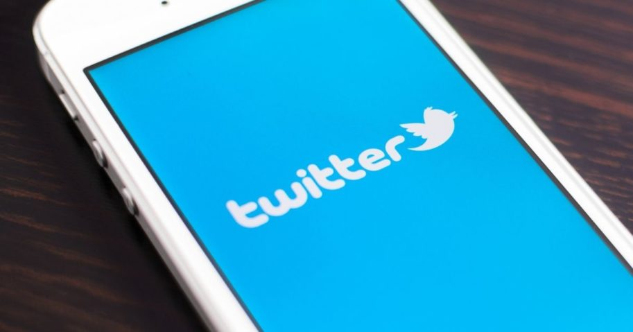 The Twitter logo is pictured on a phone in the stock image above.