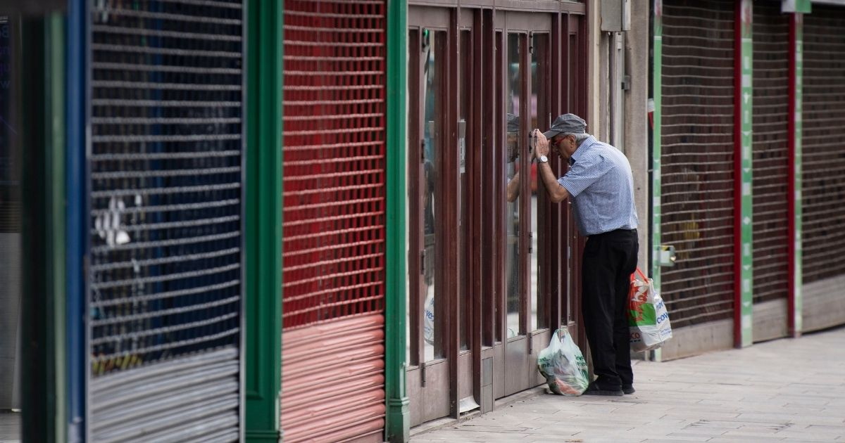 A man looking into a shuttered UK coffee shop during the country's May lockdown.