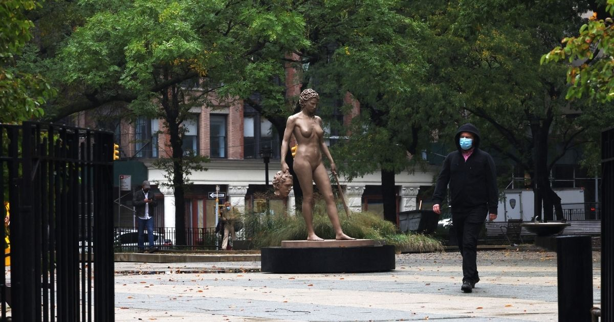 "A person walks past the newly installed statue of ""Medusa with the Head of Perseus"" by Argentine-Italian artist Luciano Garbati in New York's Collect Pond Park on Tuesday."