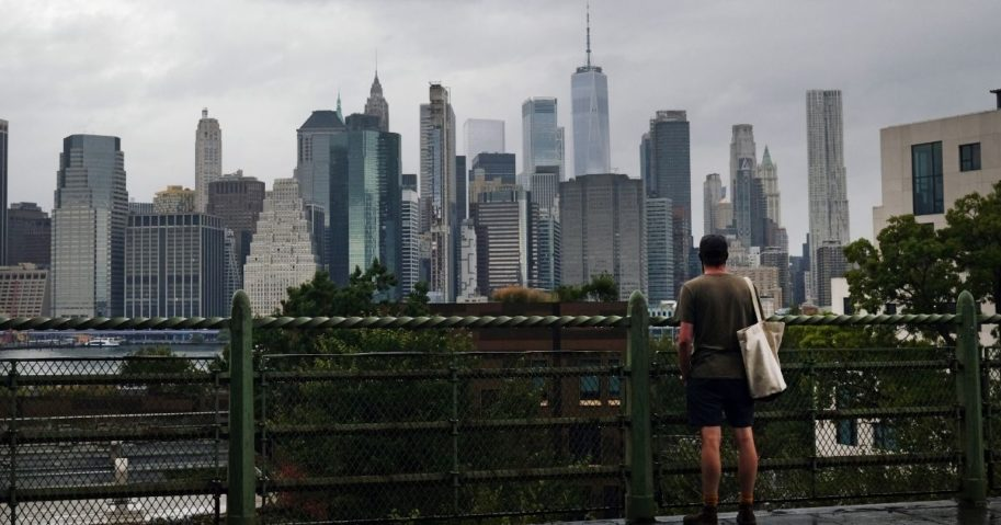 A man looks at the Manhattan skyline from a Brooklyn neighborhood on Sept. 29, 2020, in New York City, which is facing a crisis in the tourism industry.