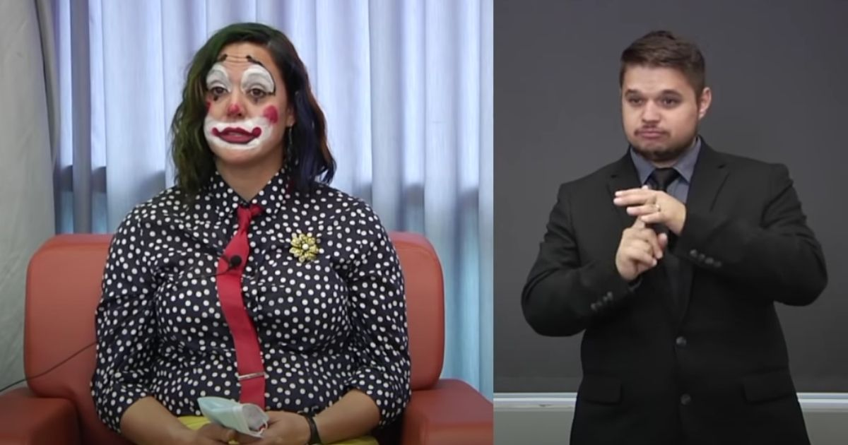 Dressed as a clown, Dr. Claire Poche, a physician with the Oregon Health Authority, announces the state's COVID-19 report on Oct. 14, 2020. At right, a sign-language expert interprets Poche's words.