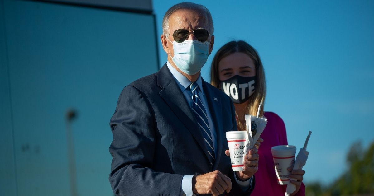TOPSHOT - Democratic presidential nominee and former Vice President Joe Biden speaks to reporters after buying two milk shakes with his granddaughter Finnegan Biden at a local hamburger place after a campaign stop in Durham, North Carolina on October 18, 2020.
