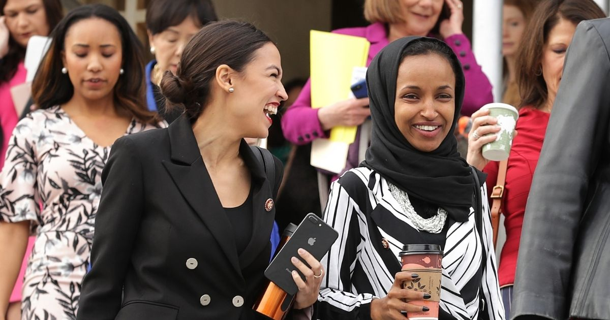U.S. Reps. Alexandria Ocasio-Cortez, left, and Ilhan Omar laugh together during a group portrait session on the steps of the Capitol in January 2019.