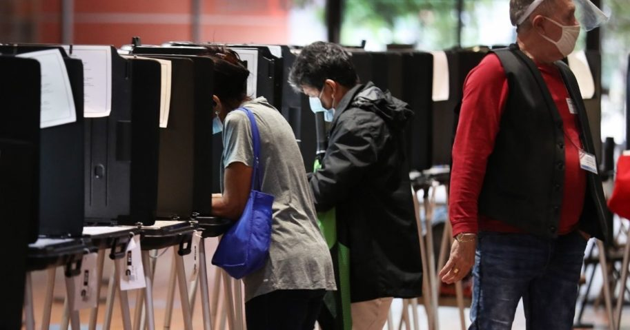 Voters fill out their ballots as they vote at the Stephen P. Clark Government Center polling station on Oct. 21, 2020, in Miami.
