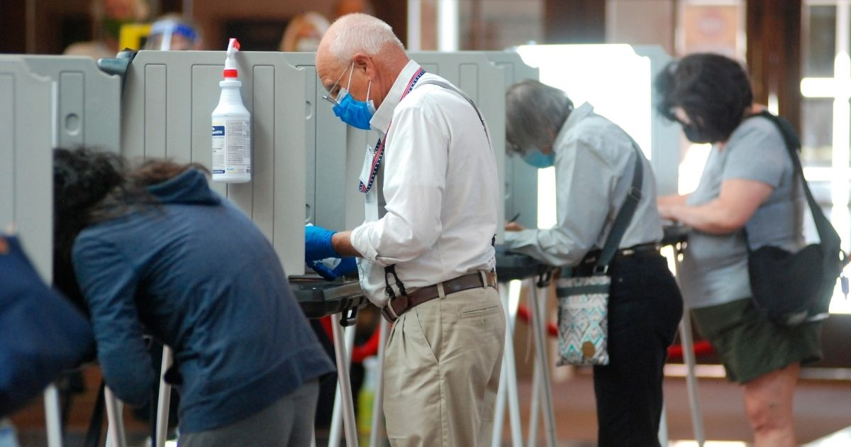 A temporary election worker disinfects voting stations while a steady stream of voters participates in the first day of balloting at the Santa Fe Convention Center in Santa Fe, New Mexico, on Tuesday.