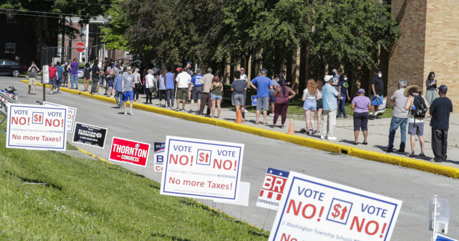 In this June 2, 2020, file photo, voters wait in a line outside Broad Ripple High School to vote in the Indiana primary in Indianapolis.