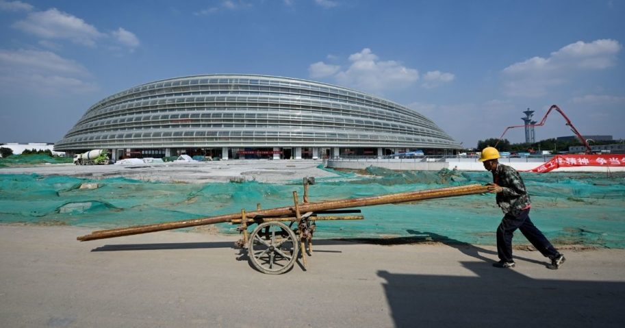 A worker pushes a wheelbarrow in front of the National Speed Skating Oval, the venue being built for speed skating events at the 2022 Winter Olympics, in Beijing on Aug. 21, 2020.
