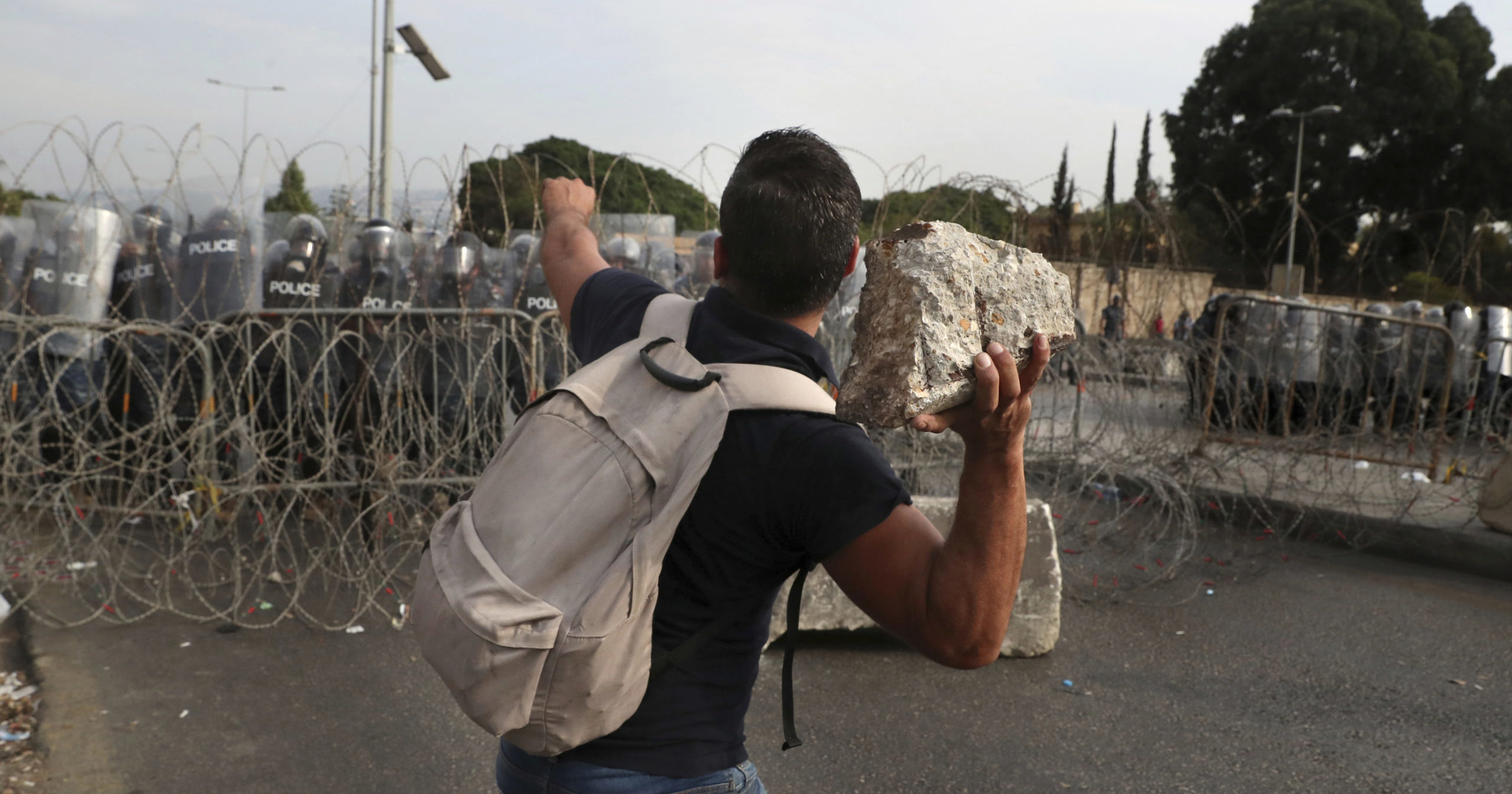 A protester throws a stone towards riot police during a protest against French President Macron's comments over Prophet Muhammad caricatures, near the Pine Palace, which is the residence of the French ambassador, in Beirut, Lebanon on Friday.