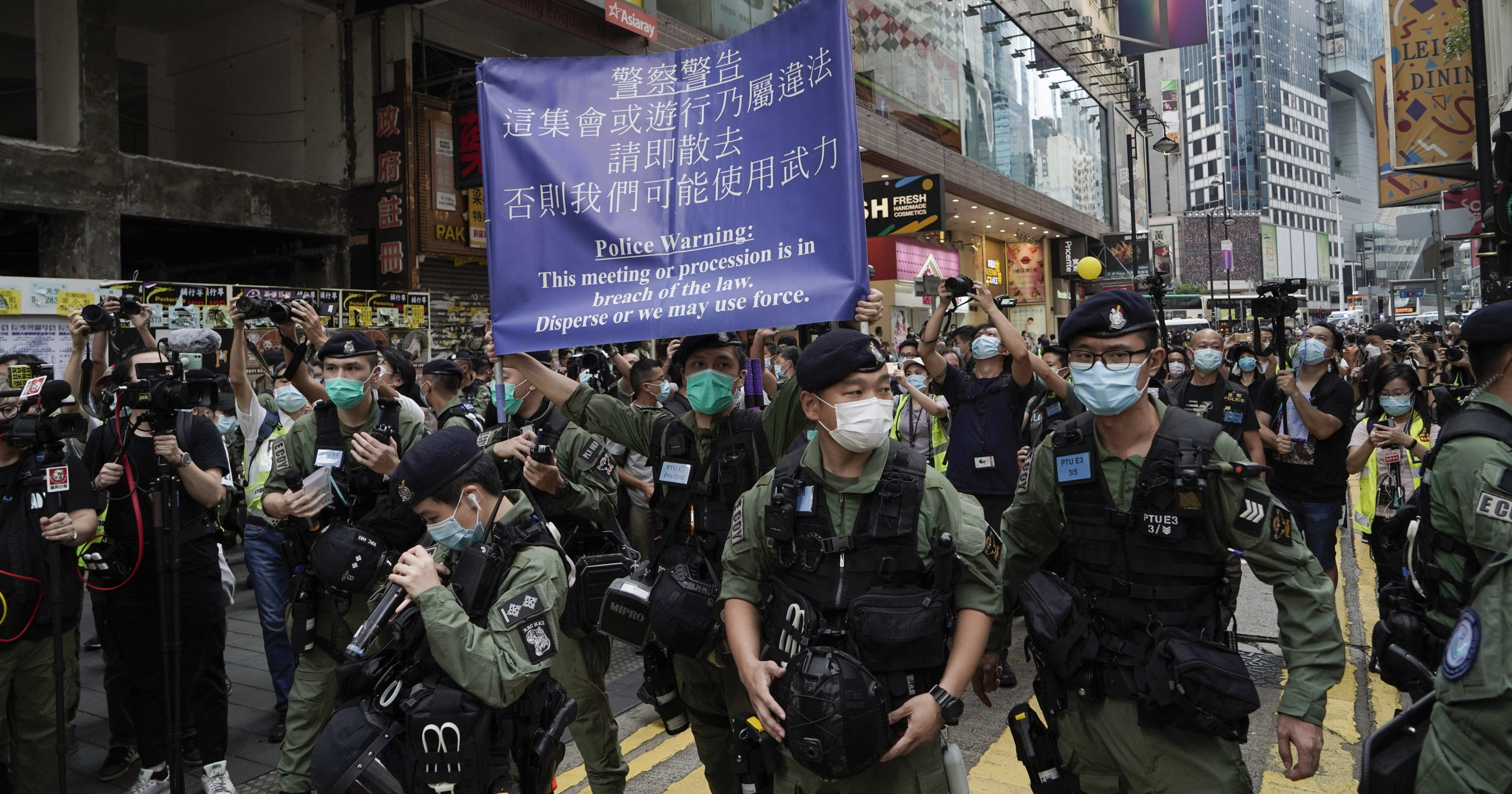 Police officers display a warning banner on China's National Day in Hong Kong on Oct. 1, 2020.