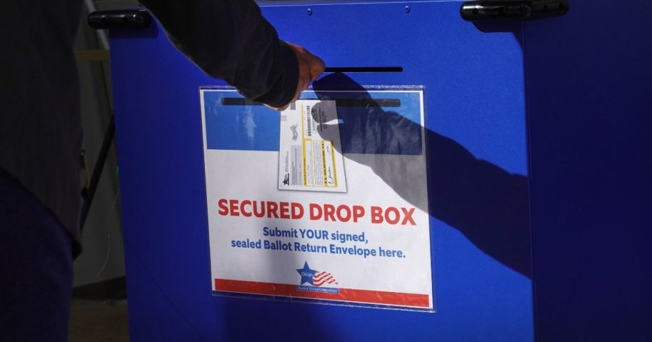 A voter drops off a mail ballot in a drop box on Oct. 2, 2020, in Chicago.