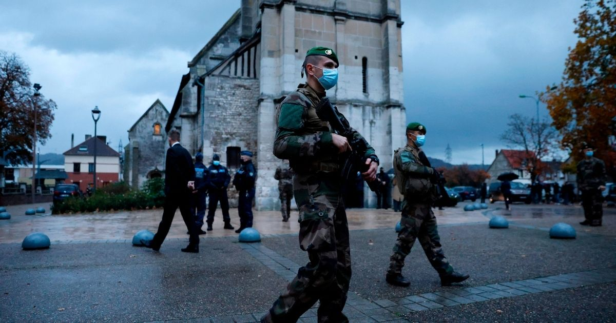 French soldiers patrol in front of a church in northwestern France on Oct. 31, 2020, two days after a knife attacker killed three churchgoers in Nice.