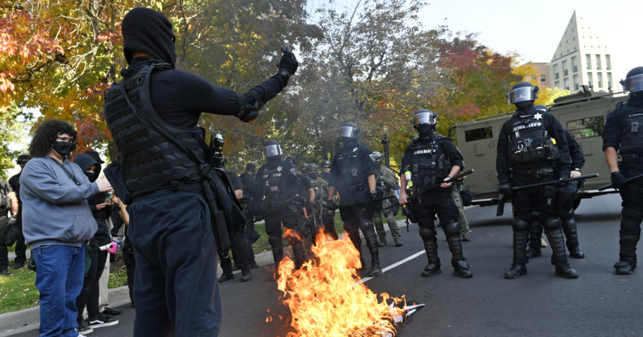 Protesters burn a police flag in front of law enforcement officers during dueling rallies between right- and left-wing groups on Oct. 10, 2020, in Denver.